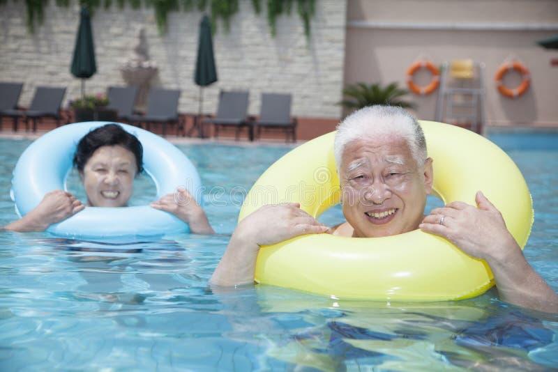 Portrait des couples supérieurs détendant dans la piscine avec les tubes gonflables image libre de droits