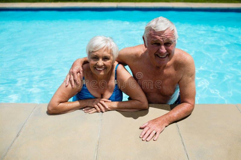 Portrait des couples supérieurs détendant ensemble dans la piscine images stock