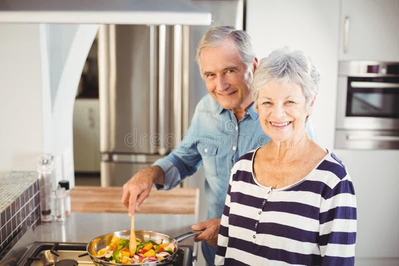 Portrait des couples supérieurs faisant cuire la nourriture photos stock