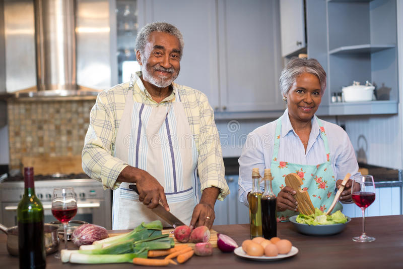Portrait des couples supérieurs préparant la nourriture à la maison photographie stock