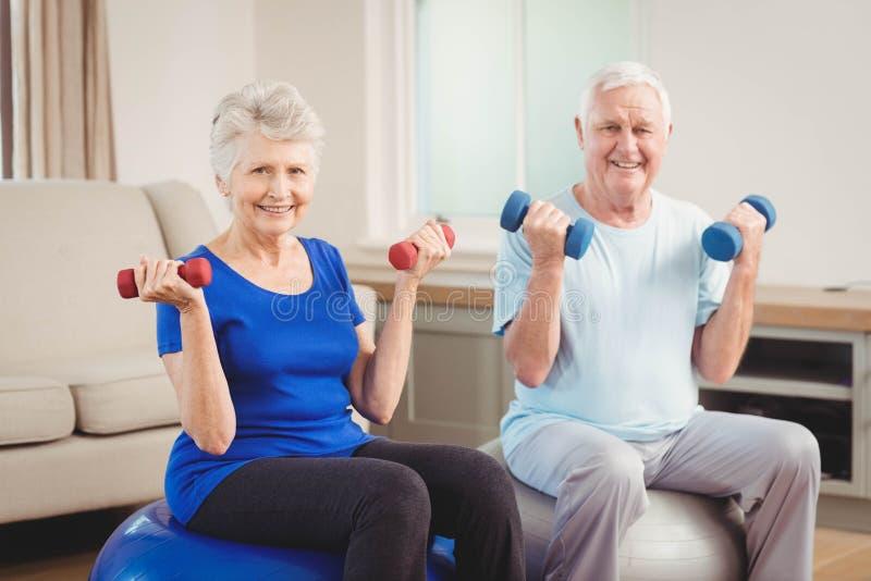 Portrait des couples supérieurs se reposant sur des boules de forme physique avec des haltères photo stock