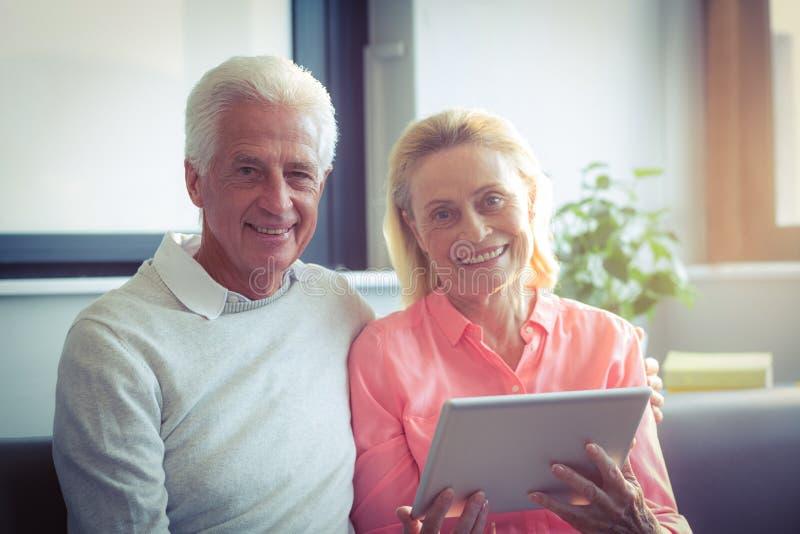 Portrait des couples supérieurs tenant le comprimé numérique image stock