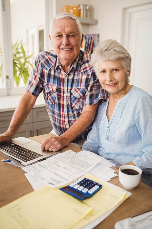 Portrait des couples supérieurs vérifiant leurs factures photo stock