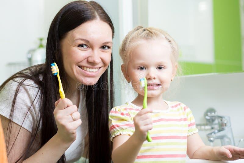 Portrait des dents de brossage de fille de mère et d'enfant dans la salle de bains photos stock