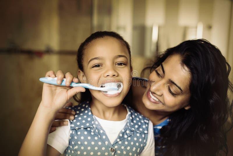 Portrait des dents de brossage de fille avec la mère dans la salle de bains photos libres de droits