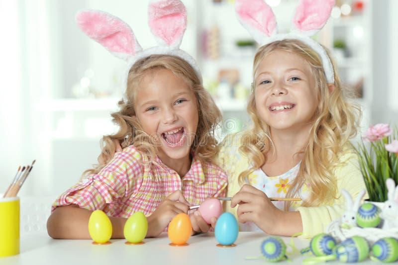 Portrait des deux soeurs mignonnes utilisant des oreilles de lapin et peignant des oeufs de pâques images libres de droits