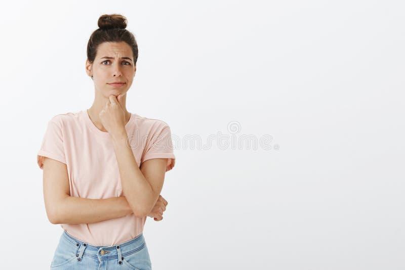 Portrait des employés de écoute contrariés de jeune directeur féminin beau tenant la main sur le froncement de sourcils réfléchi  photo stock