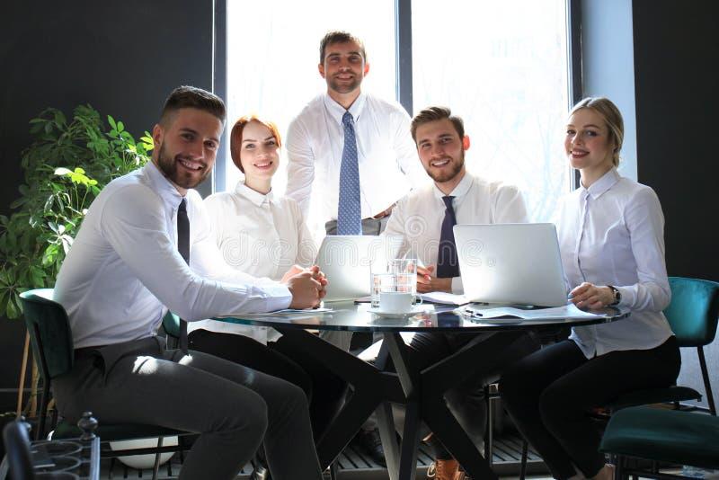 Portrait des employés positifs des affaires lors d'une réunion d'affaires de bureau image stock