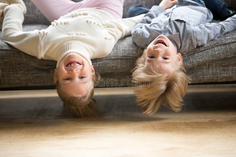 Portrait des enfants de mêmes parents garçon et du mensonge riant de fille à l'envers images stock