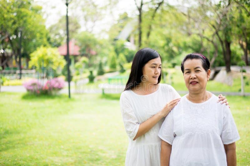 Portrait des femmes asiatiques pluses ?g? avec des jeunes femmes marchant au parc ensemble, pens?e positive photos stock