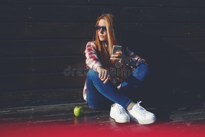 Portrait des femmes géniales à la mode causant à son téléphone de cellules pendant le temps de récréation dans le jour d'été photo stock