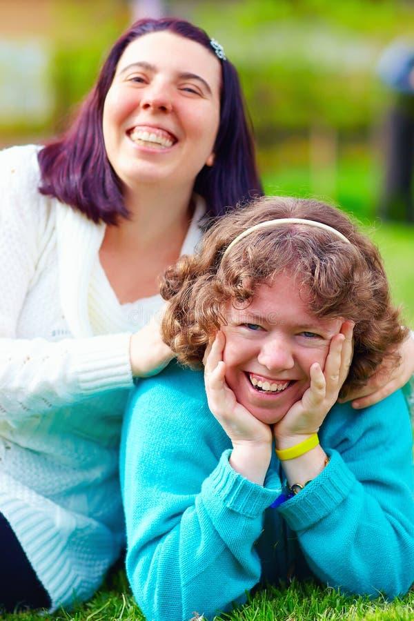 Portrait des femmes heureuses avec l'incapacité sur la pelouse de ressort photo libre de droits