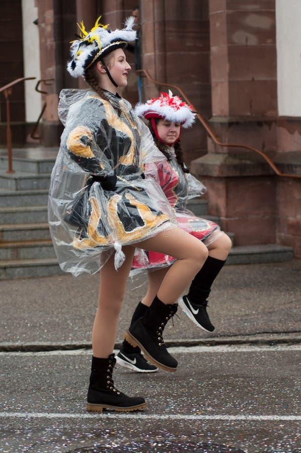 Portrait des filles de pom de pom portant avec des chaussettes et de mini jupes rouges défilant dans la rue image libre de droits