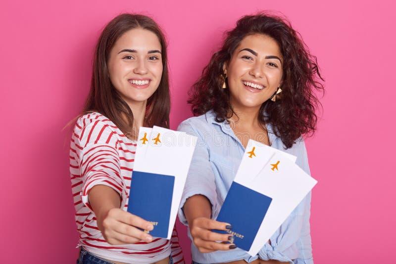 Portrait des filles mignonnes gaies voyageant en été, habillé dans des vêtements sport, montrant des passeports avec des billets  image libre de droits