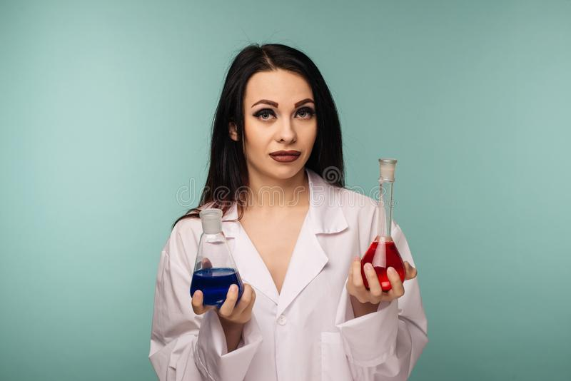 Portrait des flacons de examen de scientifique féminin avec différents produits chimiques dans le laboratoire médical image libre de droits