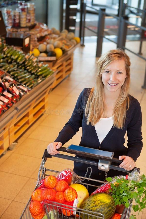 Portrait des Frauenholding-Einkaufswagens stockfoto