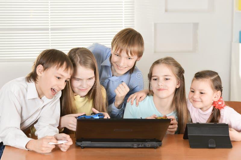 Portrait des garçons drôles et des filles jouant le jeu d'ordinateur ensemble à la table à la maison image stock