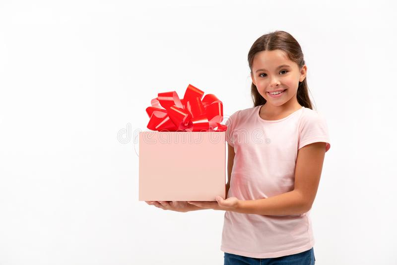 Portrait des glücklichen kleinen Mädchens mit Geschenkkasten über weißem Hintergrund stockbild