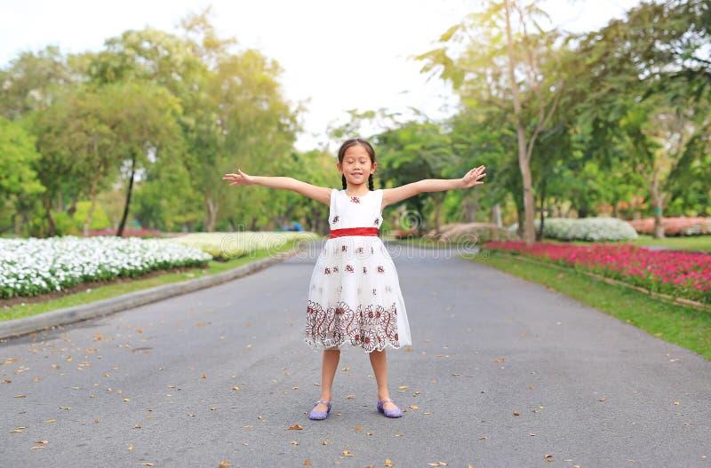 Portrait des glücklichen kleinen Mädchens mit geschlossenen Augen und öffnen Sie ihre Arme auf der Straße im Garten stehen lizenzfreie stockfotos
