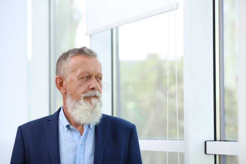 Portrait des gut aussehenden, reifen Mannes in elegantem Anzug aus Fenster stockbild