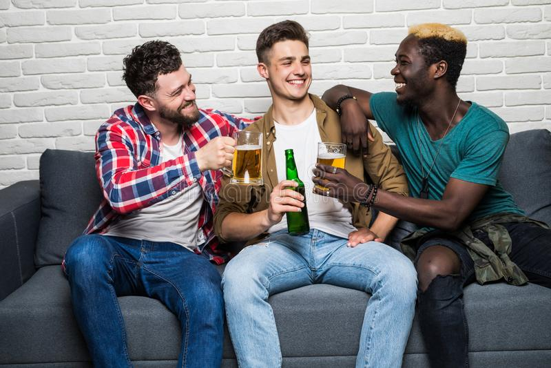 Portrait des hommes attirants, élégants, gais tenant des bouteilles avec la bière blonde allemande dans des mains, concurrence de photographie stock libre de droits