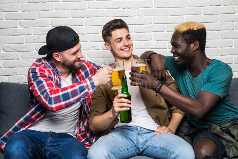 Portrait des hommes attirants, élégants, gais tenant des bouteilles avec la bière blonde allemande dans des mains, concurrence de photos libres de droits
