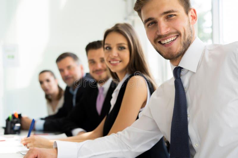 Portrait des hommes d'affaires heureux regardant l'appareil-photo se reposant dans une rangée au bureau image libre de droits