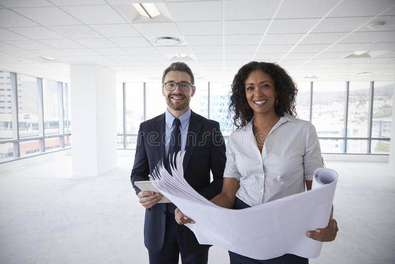 Portrait des hommes d'affaires regardant des plans dans le bureau vide photo stock