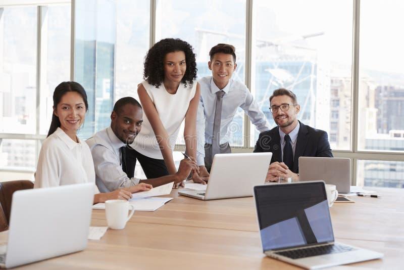 Portrait des hommes d'affaires se réunissant autour du Tableau dans le bureau photo stock