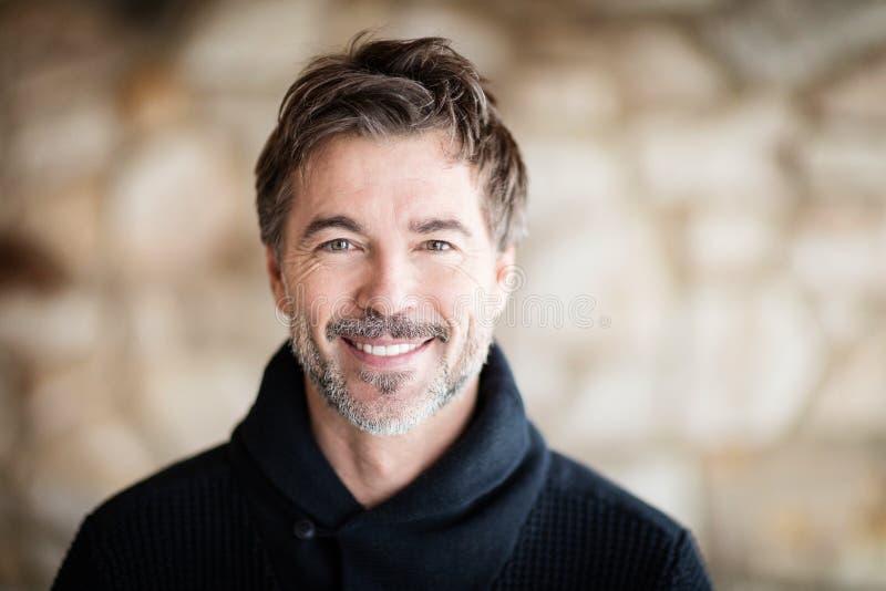 Portrait des hommes mûrs souriant à la caméra à la maison photographie stock