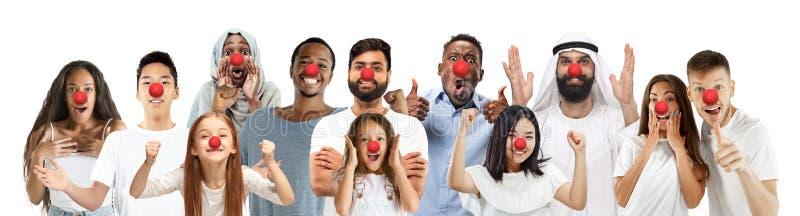 Portrait des jeunes célébrant le jour rouge de nez sur le fond blanc photos stock
