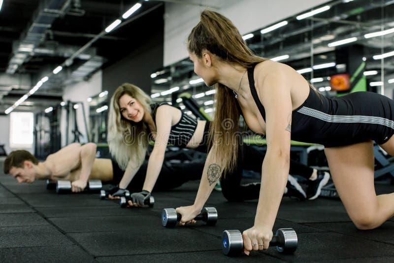 Portrait des jeunes de forme physique faisant soulevant l'exercice avec l'haltère dans le gymnase Mode de vie de personnes et con photos stock