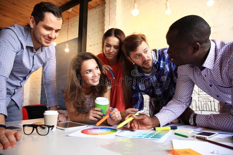 Portrait des jeunes heureux lors d'une réunion regardant l'appareil-photo et le sourire Jeunes concepteurs travaillant ensemble s image stock