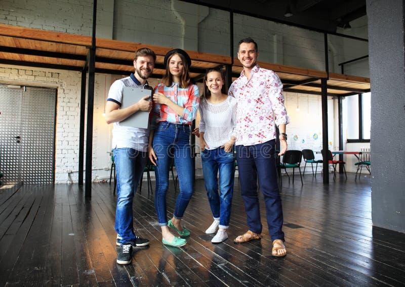 Portrait des jeunes heureux lors d'une réunion regardant l'appareil-photo et le sourire Jeunes concepteurs travaillant ensemble s photos stock