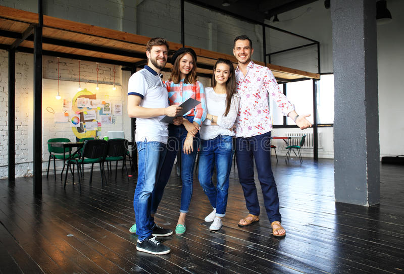 Portrait des jeunes heureux lors d'une réunion regardant l'appareil-photo et le sourire Jeunes concepteurs travaillant ensemble s image libre de droits
