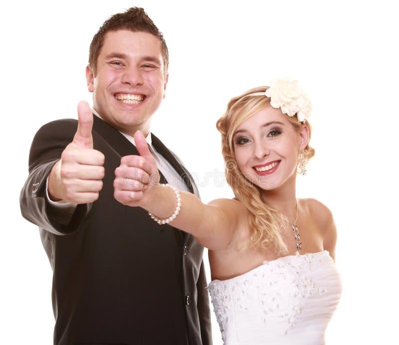 Portrait des jeunes mariés heureux sur le fond blanc image stock