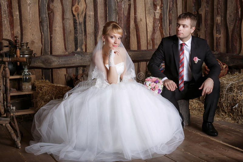 Portrait des jeunes mariés se reposant décontracté sur le fauteuil leur jour du mariage, intérieur de vintage image stock