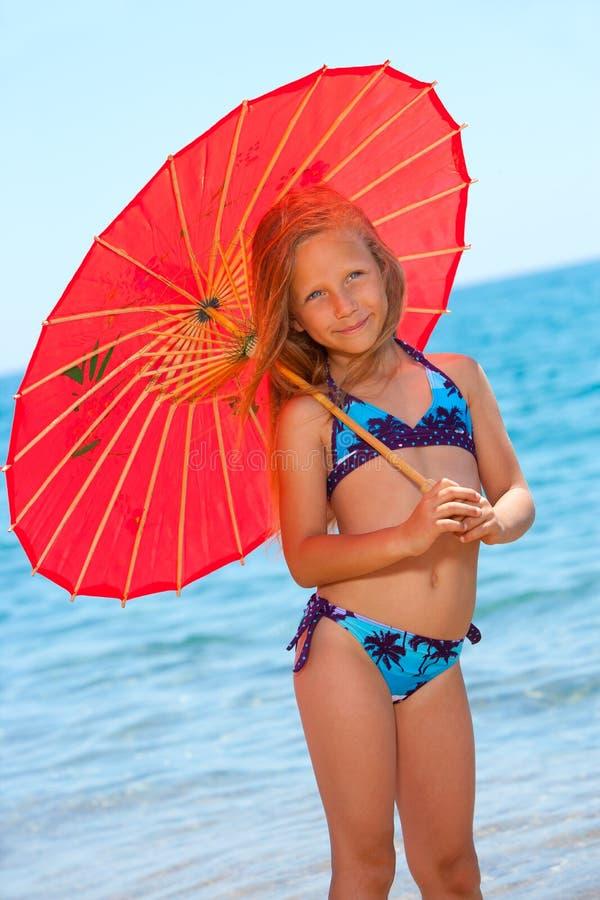 Portrait des jungen Mädchens mit Regenschirm auf Strand. stockfotografie