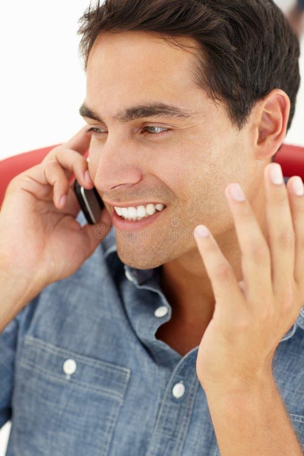 Portrait des jungen Mannes sprechend am Telefon stockbild