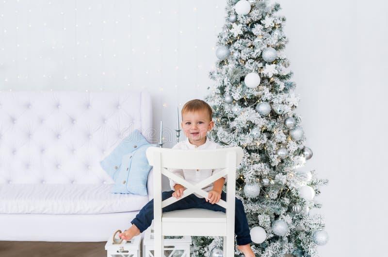Portrait des kleinen Jungen Verzierter Weihnachtsbaum Weihnachtstag im hellen Wohnzimmer Sitzen auf weißem Stuhl lizenzfreie stockfotos