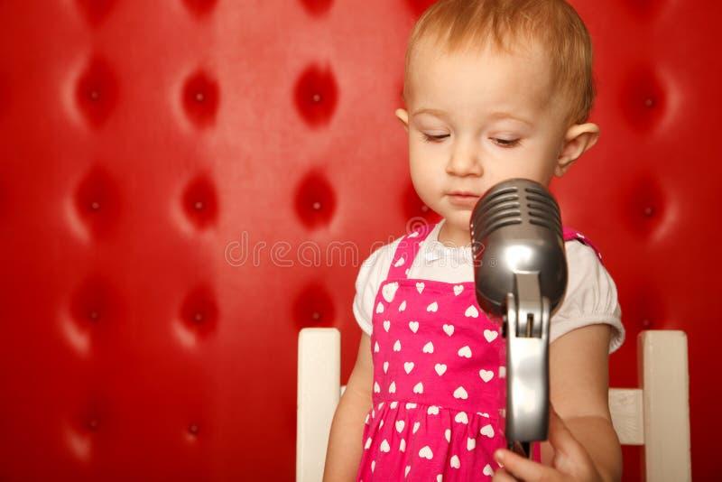 Portrait des kleinen Mädchens mit Mikrofon auf Zahnstange lizenzfreies stockfoto