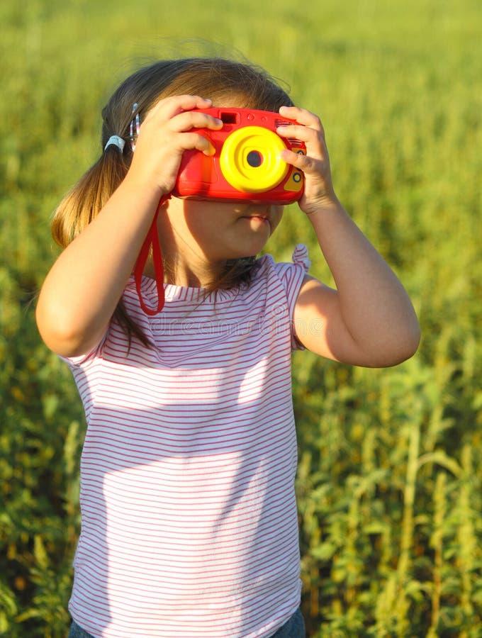 Portrait des kleinen Mädchens mit Spielzeugkamera stockfotos