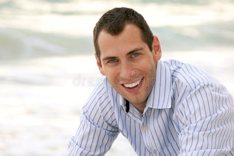 Portrait des lächelnden stattlichen Mannes, der Projektor betrachtet stockfoto