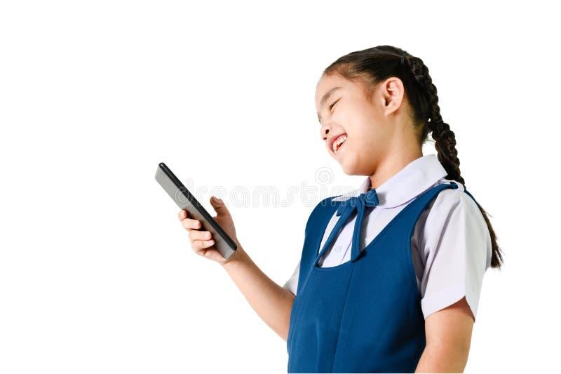 Portrait des Lächelns, kleine Mädchen in der Schule Uniform berühren den Bildschirm ein digitales Gerät, mobil, Note isoliert wei stockfotografie