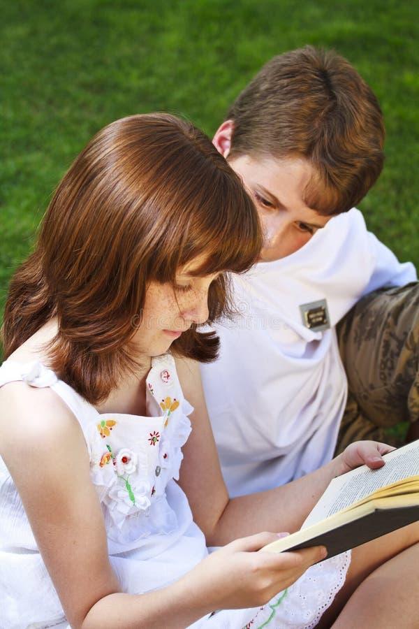 Portrait des livres de lecture mignons d'enfants dans l'environnement naturel images libres de droits