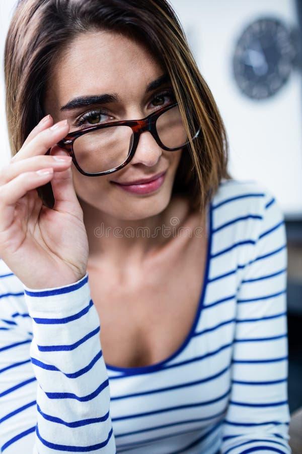Portrait des lunettes de port de jeune femme sûre image stock