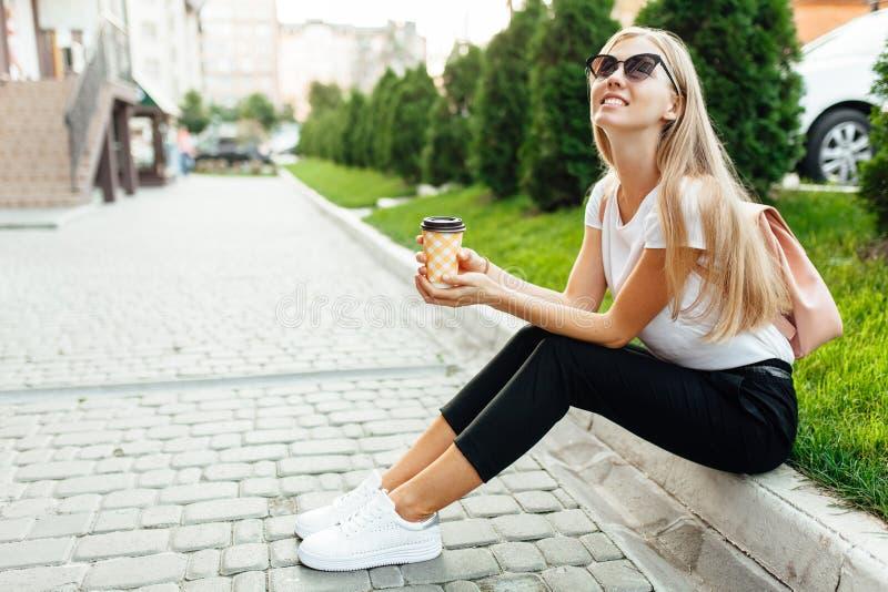 Portrait des lunettes de soleil de port d'une jeune femme dehors avec le coffe photographie stock libre de droits