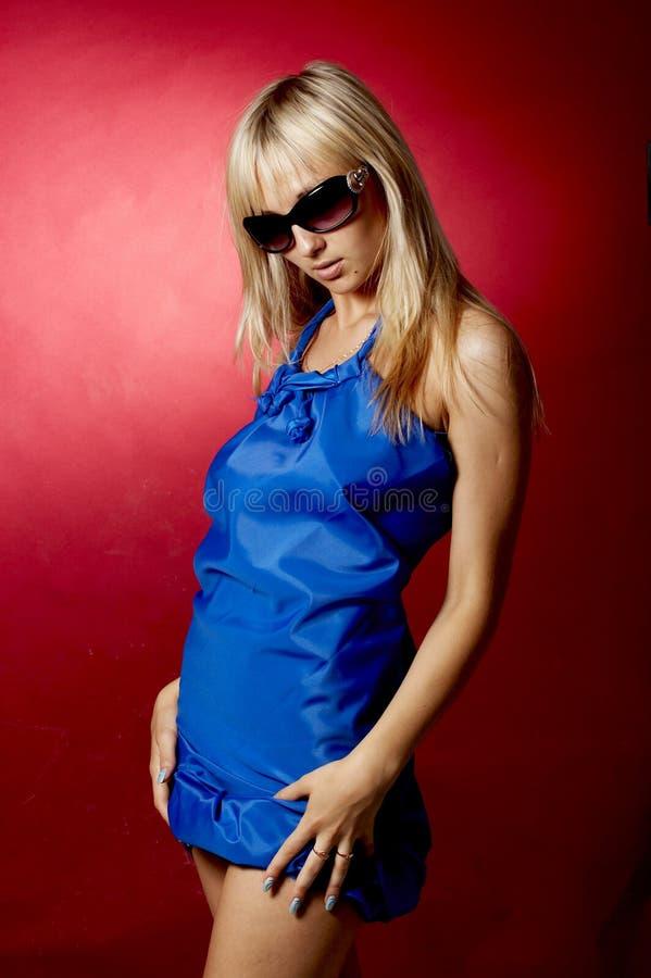 Portrait des Mädchens im Blau auf einem roten Hintergrund lizenzfreie stockbilder