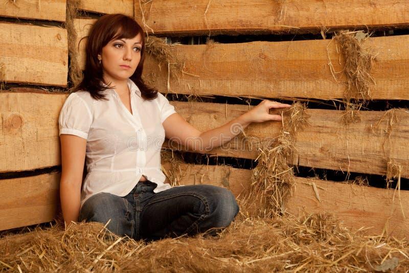 Portrait des Mädchens im weißen Hemd- und Jeanssitzen stockbild