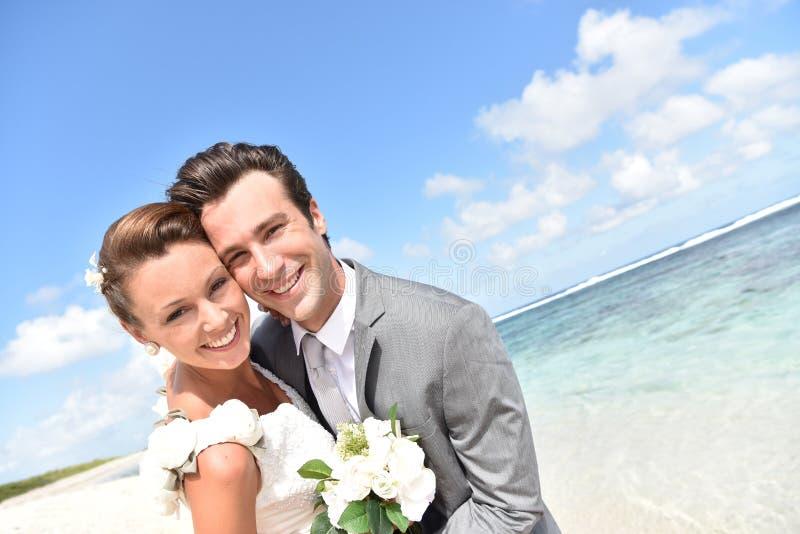 Portrait des ménages mariés fraîchement sur la plage des Caraïbes image stock